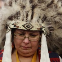 Attawapiskat Chief Theresa Spence, wearing a headdress, takes part in a drum ceremony before departing a Ottawa hotel to attend a ceremonial meeting at Rideau Hall with Gov. Gen. David Johnston in Ottawa, Friday January 11, 2013. THE CANADIAN PRESS/Fred Chartrand